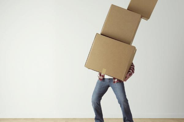 Man carrying three cardboard boxes