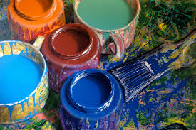 Pots filled with different coloured paints and brushes