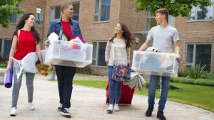 Four students carrying items from housing