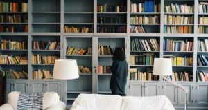 lady looking through bookcase in living room