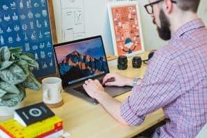man using macbook pro at desk