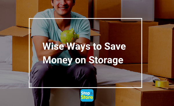 Man holding green piggy bank sitting near to storage boxes